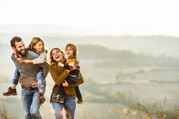 Junge glückliche Familie genießen im Herbst Spaziergang auf einem Hügel. – Foto