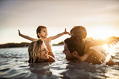 Happy parents and their small kids having fun in sea at sunset.