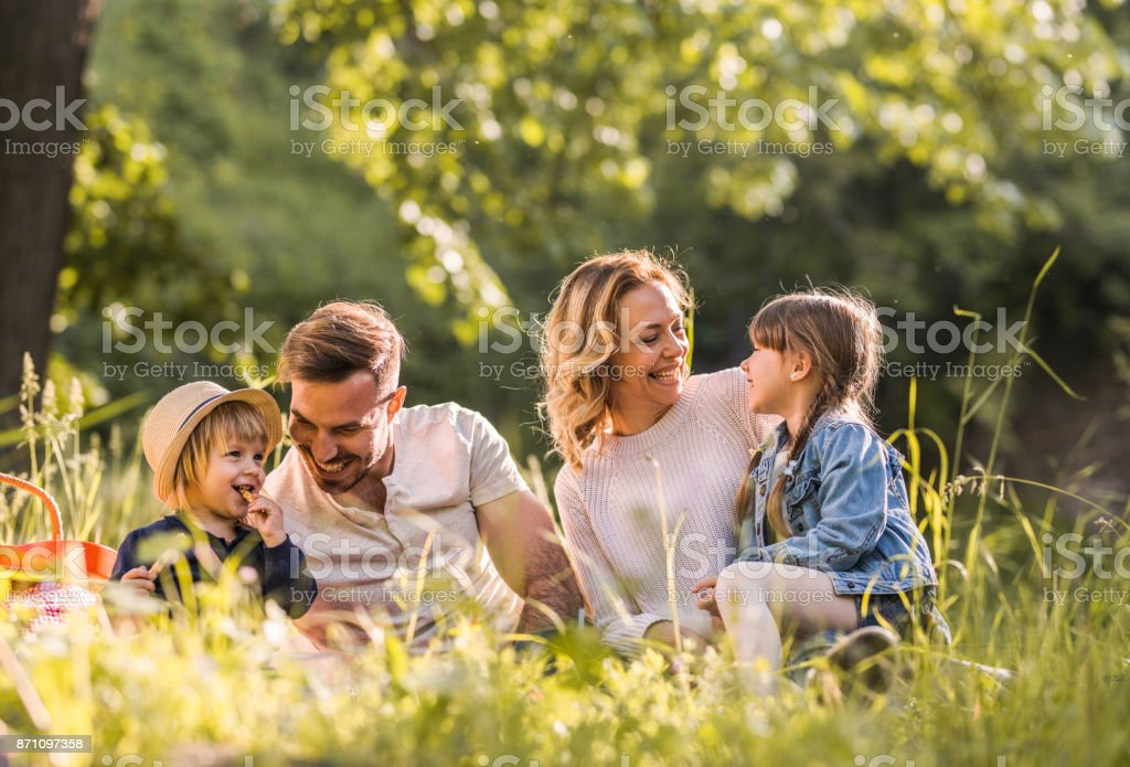 Young happy family enjoying on picnic during spring day in the forest. stock photo