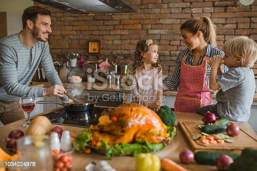 Happy parents talking to their small kids while preparing a meal for Thanksgiving day in the kitchen.