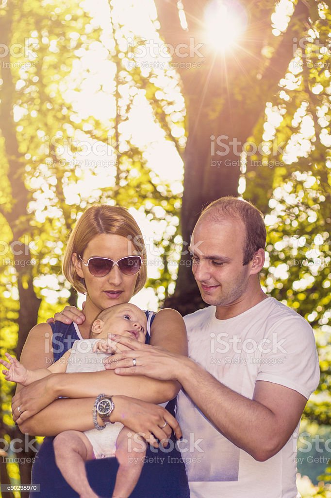 Young happy, family father and mother holding baby on sunset royaltyfri bildbanksbilder