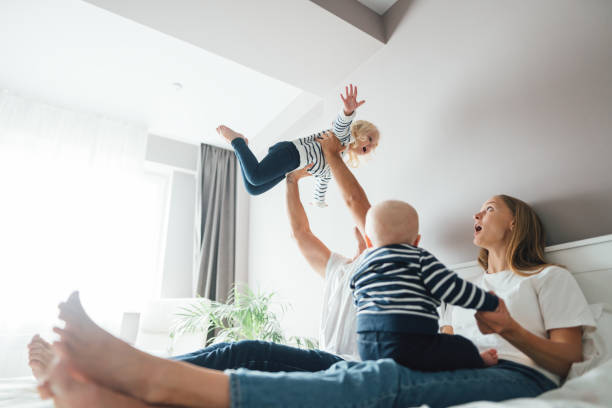 Junge glückliche Familie haben Spaß zusammen mit ihren Kindern zu Hause. Papa wirft auf und fängt ihre Tochter, während Mutter mit Sohn spielen – Foto