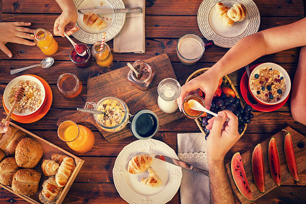young happy family having breakfast - breakfast stock photos and pictures
