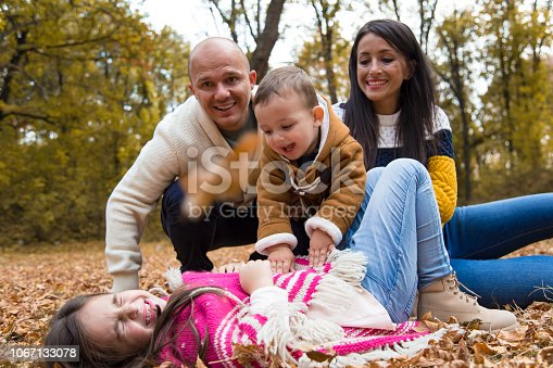 Young happy family having fun in public park