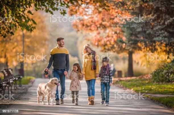 Young happy family holding hands while taking their dog for a walk in picture id991971128?b=1&k=6&m=991971128&s=612x612&h=6hl7av jje7bwdfsx3tdic9ctj7r 3hnfdweyaoo6fe=