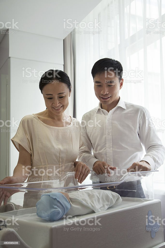 Young happy family looking down at their newborn stock photo