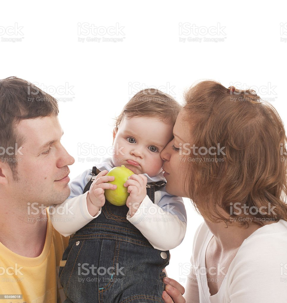 Young happy family: mother, father and baby with green apple royalty-free stock photo