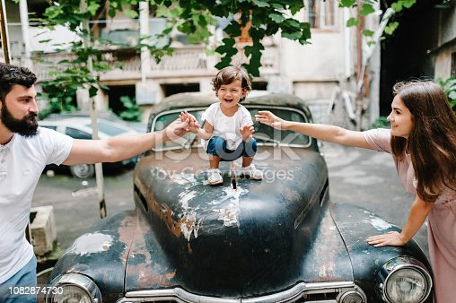 Young happy family: mother, father, baby daughter during a walk the streets near ancient, vintage car of the old city, town, outdoors. The concept of family holiday and travel.