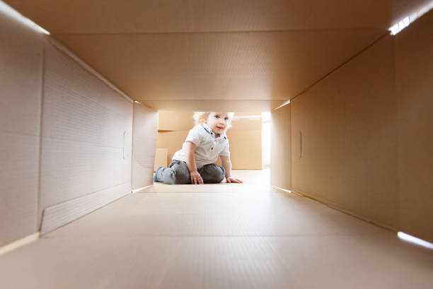 junge glückliche familie zieht in eine neue wohnung. kleines baby in einem karton - kinder verpackung stock-fotos und bilder