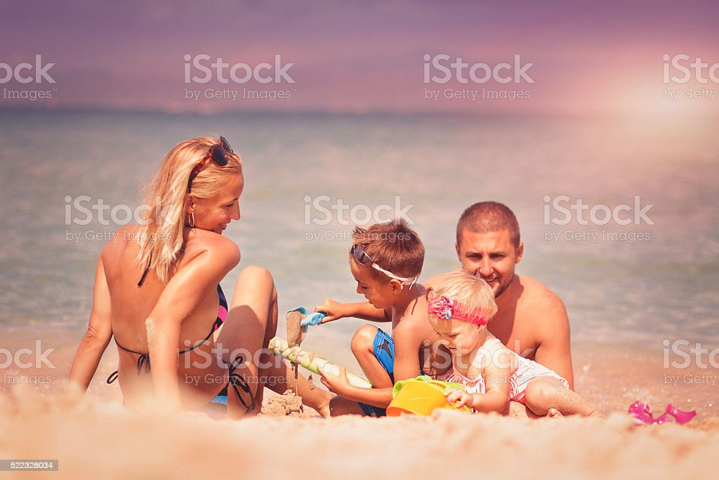 Young happy family playing with sand at beach stock photo