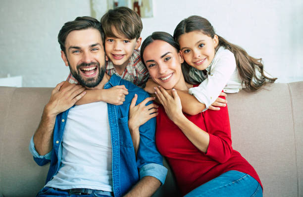 young happy family relax together at home smiling and hugging - family stock pictures, royalty-free photos & images