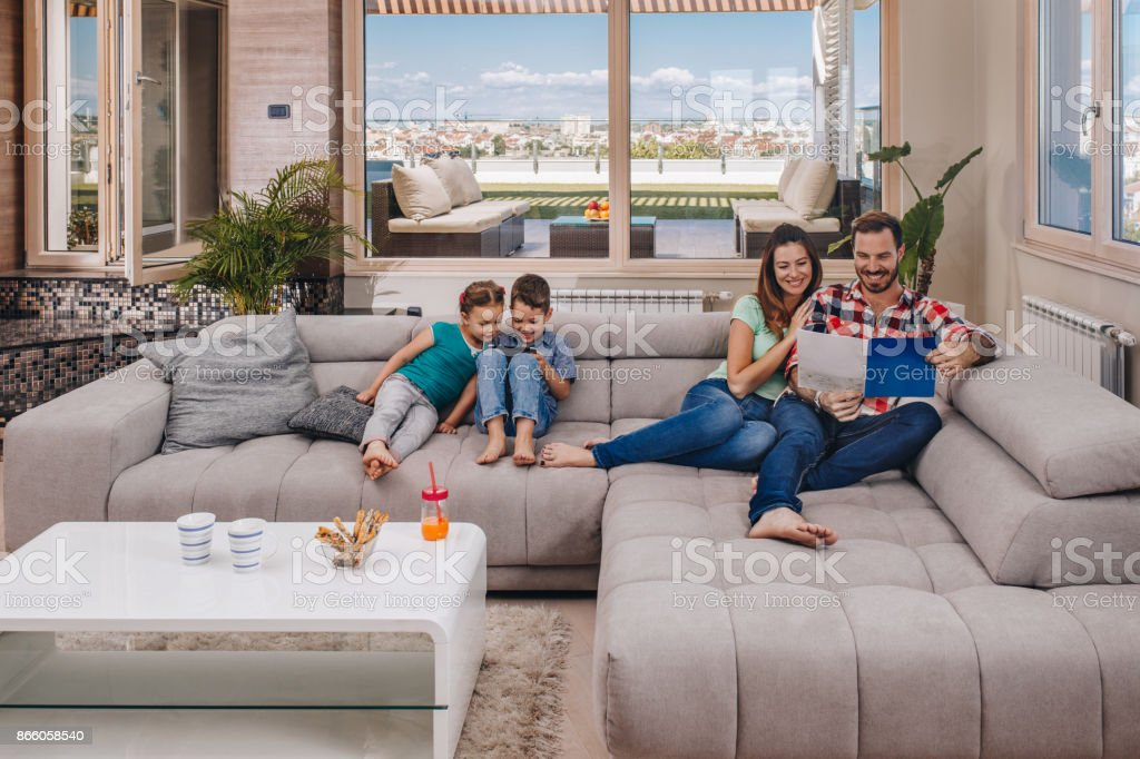 Young happy family relaxing on sofa at their penthouse.