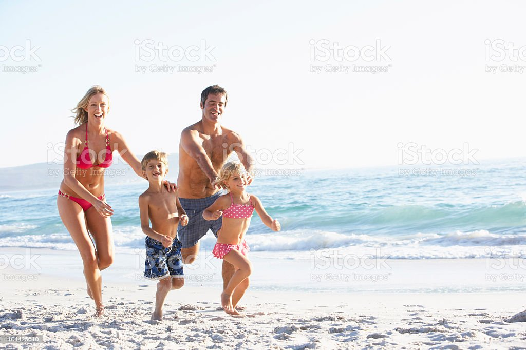 Young happy family running along the coast on holiday royalty-free stock photo