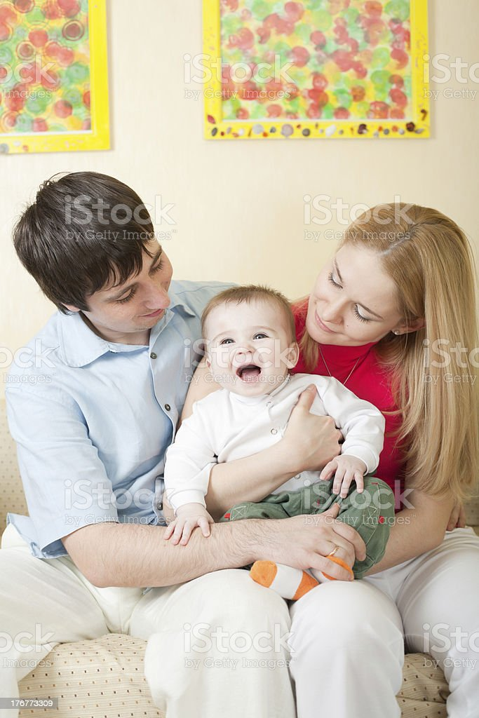 Young happy family sitting on sofa at home royalty-free stock photo