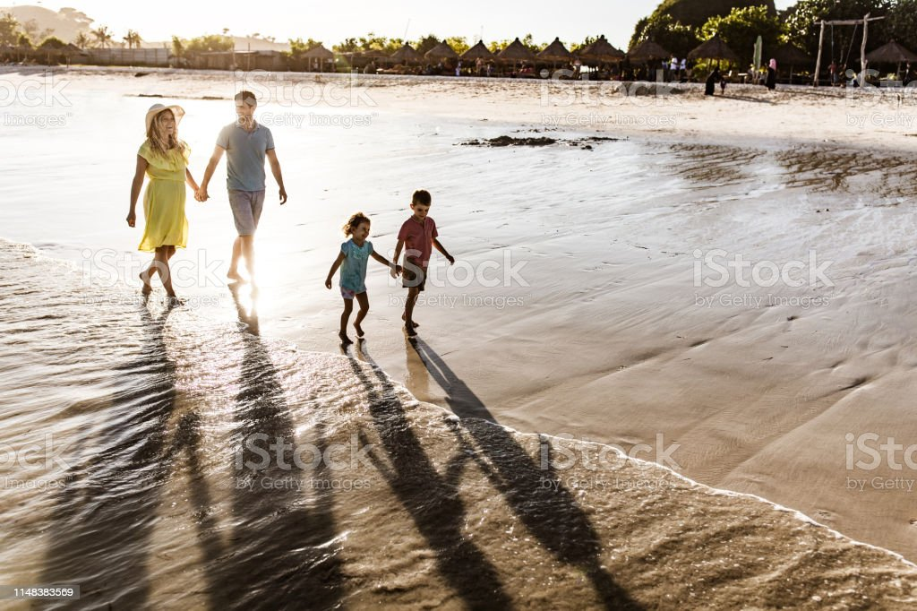 Happy parents holding hands while walking behind their kids on the...