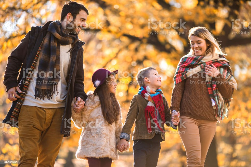 Happy parents and their small kids holding hands while walking in the...