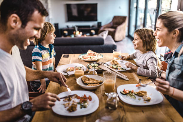 Young happy family talking while having lunch at dining table. Happy family communicating during lunch time in dining room. Focus is on kids. four people stock pictures, royalty-free photos & images