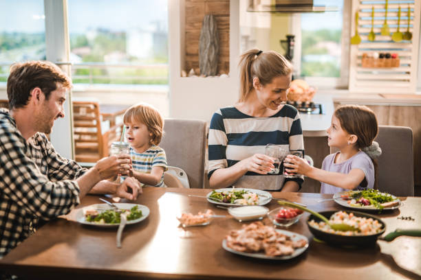 Junge glückliche Familie Toasting während der Mittagszeit am Esstisch. – Foto