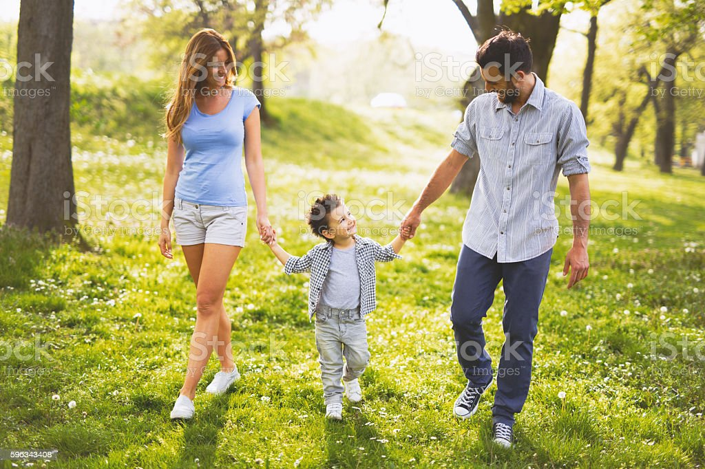 Young happy family walking through the park holding hands. royalty-free stock photo