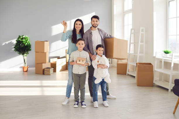Young happy family with children enjoying new apartment together stock photo