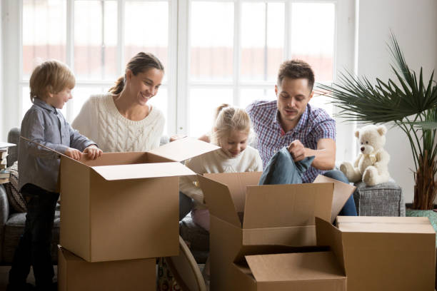 Young happy family with children packing boxes on moving day - foto stock