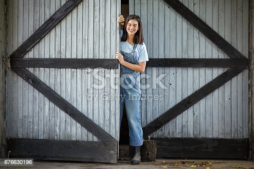 Young woman working on a farm is opening the door of a barn or shed