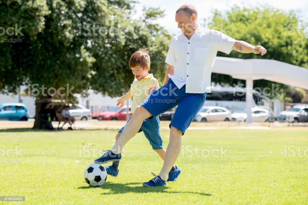 young happy father and excited 7 or 8 years old son playing together soccer football on city park garden running on grass kicking the ball in dad and boy relationship and healthy sport lifestyle stock photo