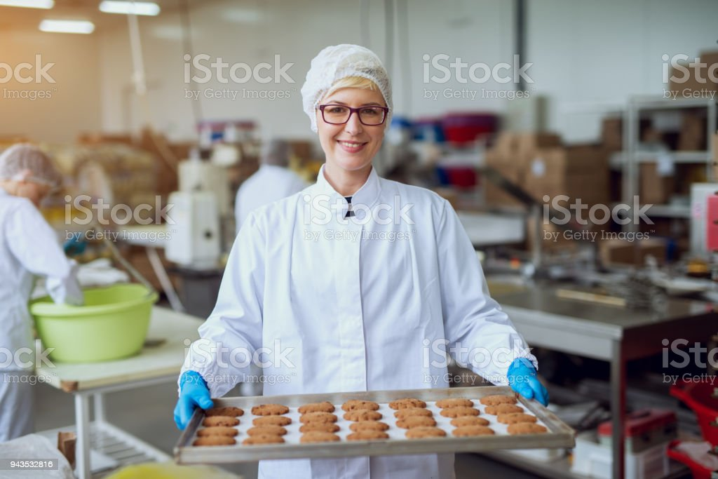 Jeune travailleur féminin heureux en chiffons stériles tenant fraîchement biscuits sur fer-blanc à l'intérieur de l'usine de production d'aliments cuits au four. - Photo