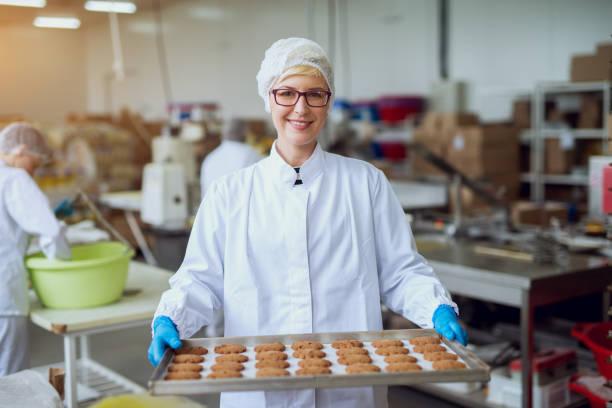 ung glad kvinnliga arbetstagare i sterila dukar håller färska bakade cookies på vitplåt inuti produktion matfabriken. - livsmedelstillverkningsfabrik bildbanksfoton och bilder