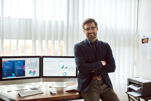 Young happy financial analyst in classic wear and eyeglasses leaning against a table and smiling at camera while working with statistical data, graphs and charts on computer in the modern office