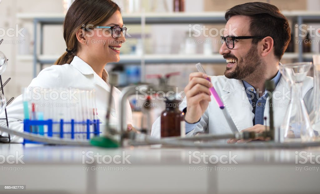 Young happy forensic scientists communicating while working in a laboratory. stock photo