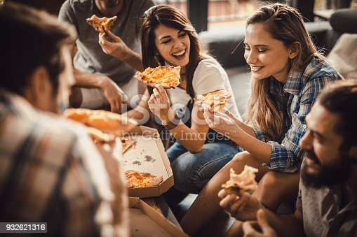 Group of happy roommates having fun while eating pizza for lunch in the living room.