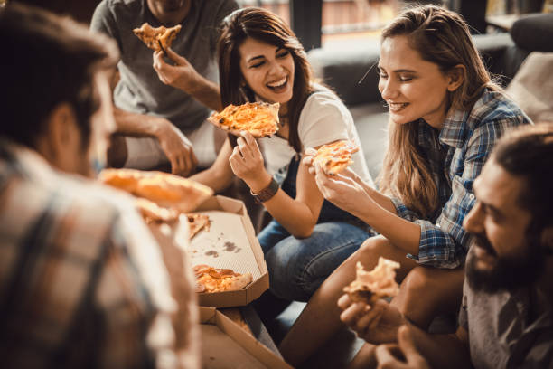Young happy friends having fun while eating pizza at home picture id932621316?b=1&k=6&m=932621316&s=612x612&w=0&h=mo6vo miyvlatqnd4wfmqgf0pnmdp8g1if75zvaeypc=