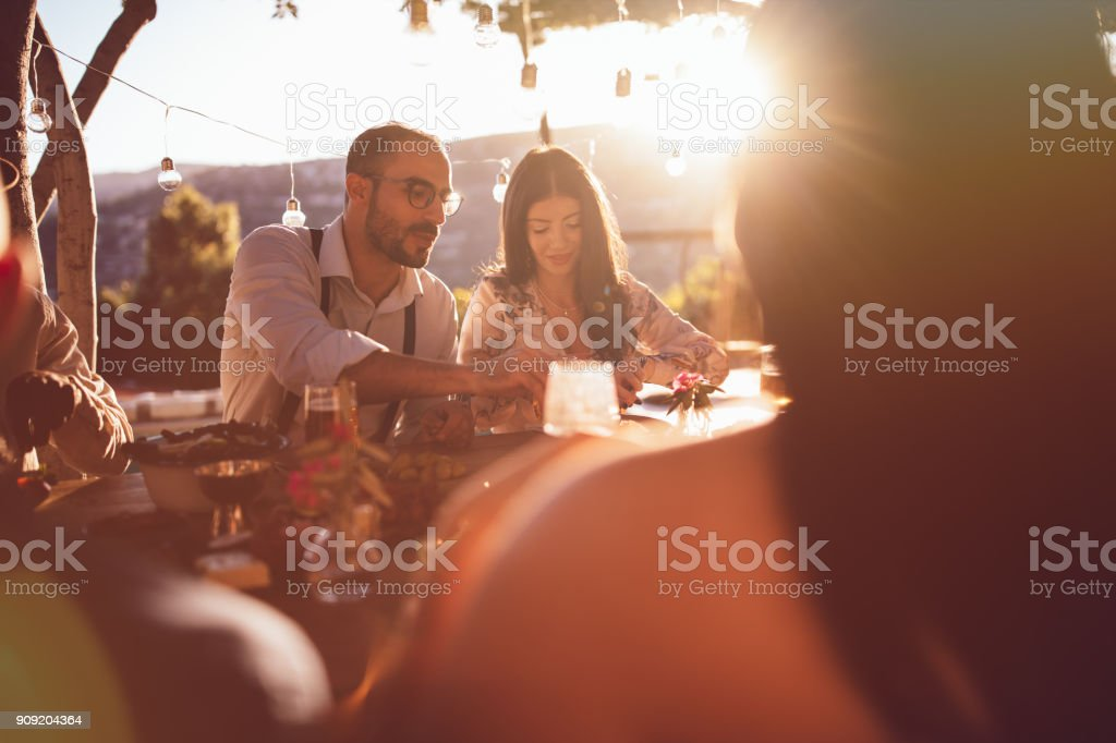 Young happy friends having lunch at mediterranean countryside cottage stock photo