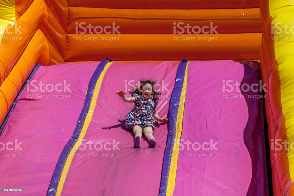 Young happy girl child in dress riding inflatable slide outdoors a warm summer day. royalty-free stock photo