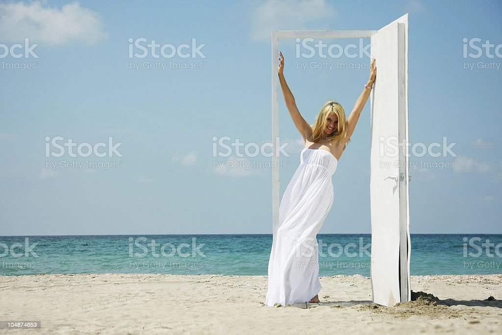 young happy girl entering open door on sea background royalty-free stock photo