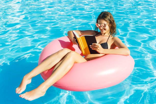 glückliches mädchen im bikini ist das schwimmen im pool und einem buch mit einem rosa kreis - pool rund stock-fotos und bilder