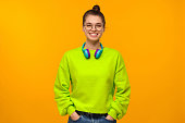 istock Young happy girl in green neon sweatshirt and jeans, wearing wireless headphones around neck, keeping hands in pockets, isolated on yellow background 1257722840