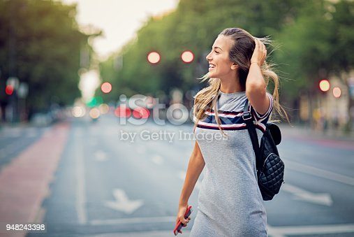 Young, happy girl is crossing the street at the crosswalk