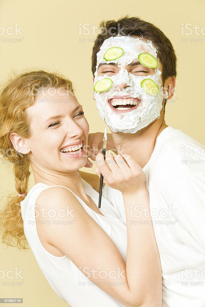 Young happy girl preparing a facial mask for her partner stock photo