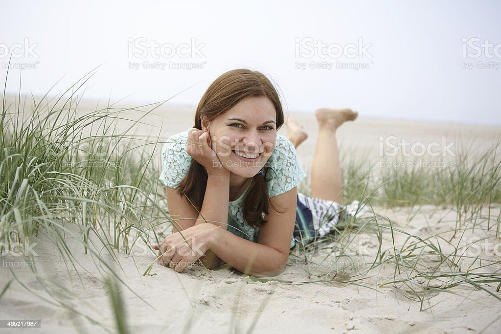 Young happy girl relaxing on sand dunes stock photo