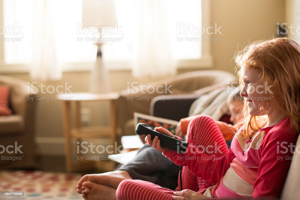 Young, happy girl watches tv stock photo