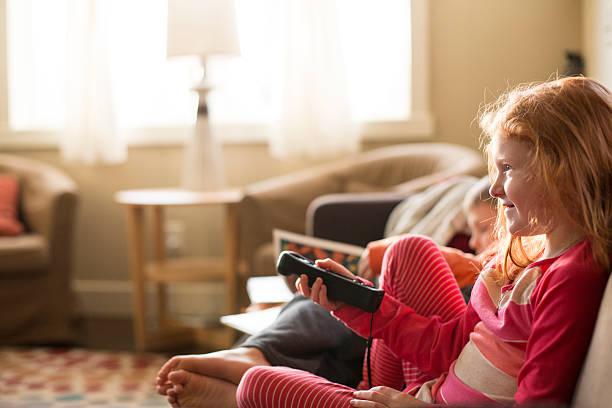 giovane ragazza felice orologi tv, - divano procrastinazione foto e immagini stock