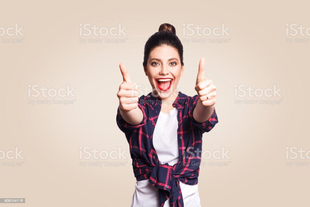 Glückliches Mädchen mit lässigen Stil und Bun Haar Daumen hoch ihr Finger auf Beige leere Wand mit textfreiraum Blick in die Kamera mit toothy Lächeln. – Foto