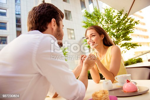 Young happy gorgeous lady is sitting in light cafe`s terrace outdoors on a sunny day and enjoy with her partner, smiling, looking at him