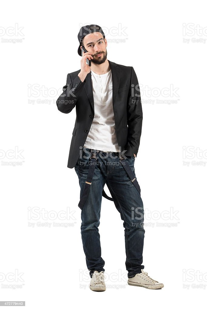 Young happy guy talking on the cellphone wearing cap backwards stock photo