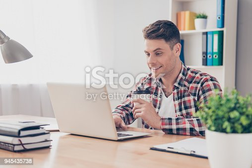 istock Young happy guy with cup of coffee using laptop 945435738