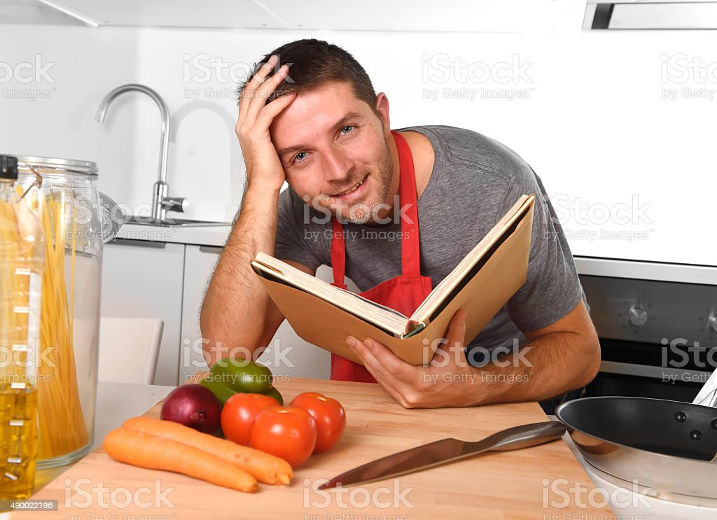 Young happy home cook man reading recipe book learning cooking stock young happy home cook man reading recipe book learning cooking royalty free stock photo forumfinder Gallery