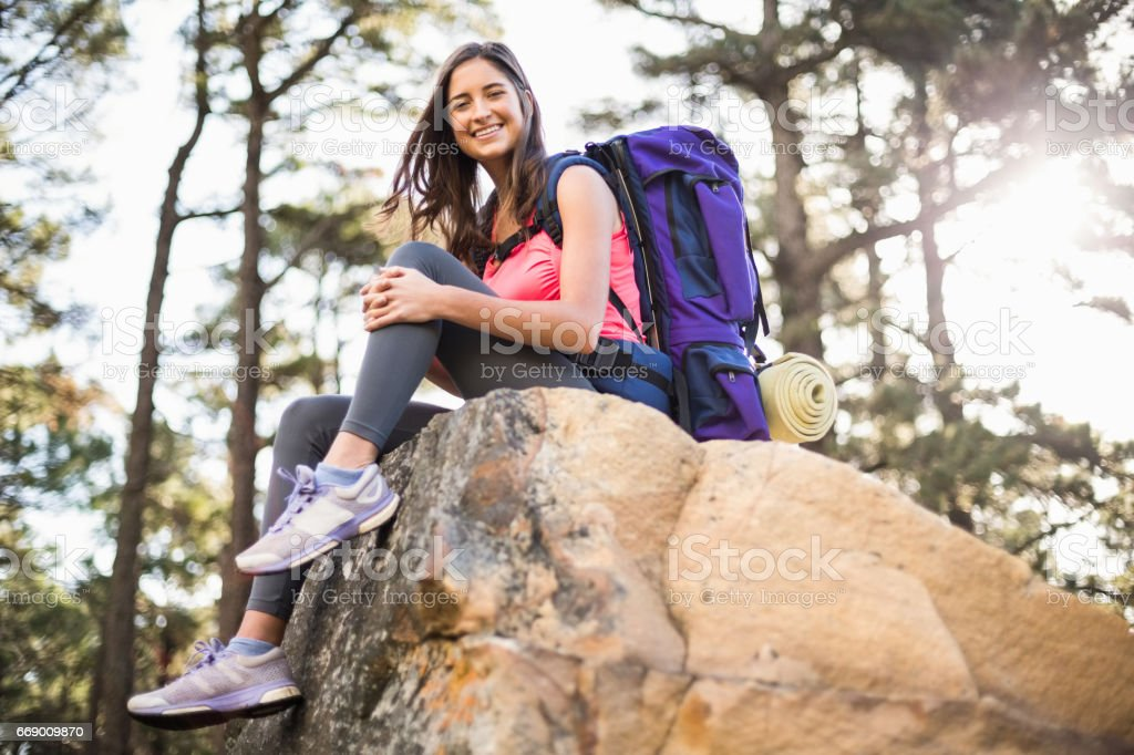 df62389642c Young happy jogger sitting on rock and looking at camera royalty-free stock  photo