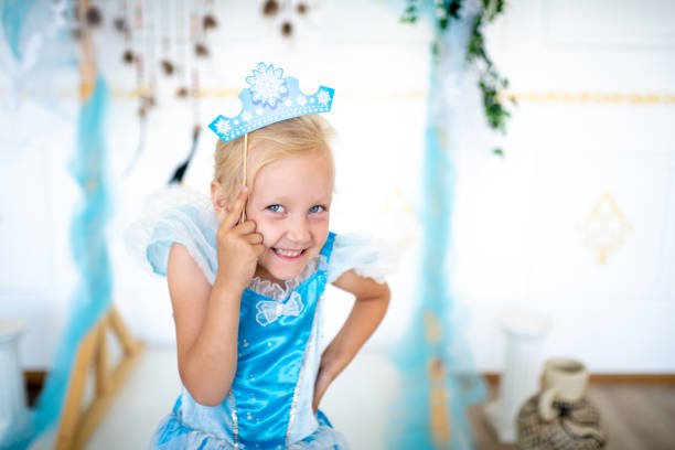 young happy kid Prepare for the new year party, the snow queen or the Snow Maiden princess. Beautiful girl with a cardboard caron. Blonde holding a decoration on a wooden stick. Original accessories for photo shoots carnival children stock pictures, royalty-free photos & images